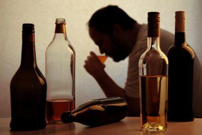 Man in background drinking-bottles in foreground